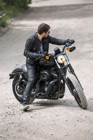 Cool man with a beard on the black motorcycle on the dirt road on the nature background. He looks to the left. He wears black jeans, a dark-gray T-shirt with a print, black shoes, black gloves, a black leather jacket and sunglasses. Photographed from the