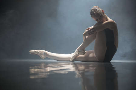 clasps: Young ballerina sitting on the floor in the dance hall. She clasps her hands one leg while the other leg is stretched forward. She is reflected on the floor surface. Smoke curled behind her. Light falls from above. Low key photo.