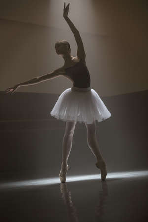 pointes: Pretty ballerina posing in leotard with white tutu in the dark dance hall. She is standing on the pointes with outstretched arms. Light falls down from above behind her. Low key photo. Stock Photo
