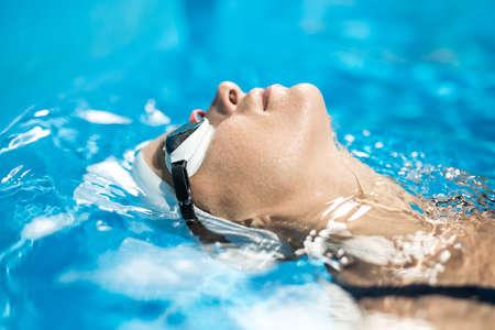 Horizontale close-up-Foto von weiblichen Schwimmer im Schwimmbad. Mädchen schwimmt auf dem Rücken. Sie trägt eine weiße Badekappe und Schwimmbrille. Schießen von der Seite.