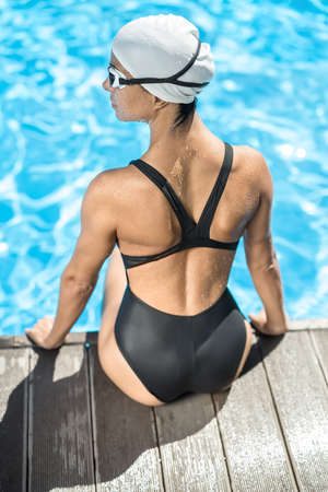 swim cap: Back view of the sportive girl who sits on the pool side in the swimming pool outdoors. She wears a black swimsuit, a white swim cap and swim glasses. Her head turned to the left side. Vertical.