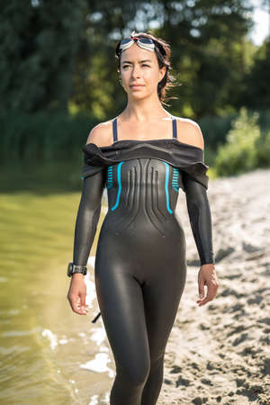 Beautiful sportive woman in a dark swimrun suit stands on the lake waterfront outdoors. She has swim glasses on the head and a stopwatch on the right hand. Sun shines at her body. Vertical. Stock Photo