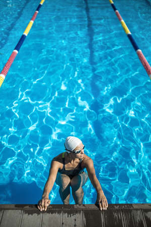 swim cap: Pretty female swimmer in the swimming pool. Woman wears a black-lime swimsuit, a white swim cap and swim glasses. She looks to the left and holds her hands on the pool side. Outdoors. Vertical. Stock Photo