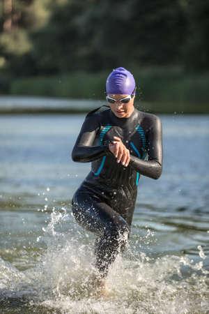 Amazing female runner runs on the water outdoors. She wears dark swimrun suit, violet cap, swim glasses. Girl looks at the stopwatch. Water splashes are around her body. Sun shines at her body.