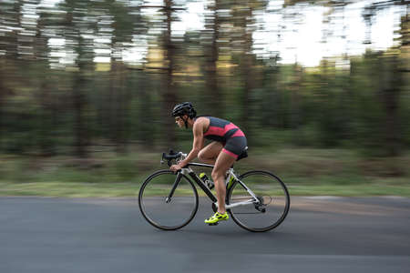 Energetic sportive girl rides a bike on the road on the nature background. She wears black-pink sportswear, a black helmet, sunglasses and green sneakers. Shoot from the side. Horizontal. Stock Photo