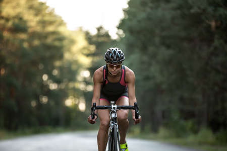 Sportive girl rides a bike on the road on the nature background. She wears black-pink sportswear, a black helmet, sunglasses and green sneakers. Horizontal.