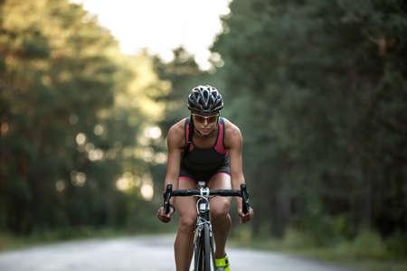 Sportive girl rides a bike on the road on the nature background. She wears black-pink sportswear, a black helmet, sunglasses and green sneakers. Horizontal. Zdjęcie Seryjne - 62766502