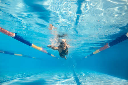 swim cap: Motion photo of a girl who swims underwater in the swim pool outdoors. She wears a black-gray swimsuit with patterns, a white swim cap and swim glasses. Sunlight falls from above. Horizontal.
