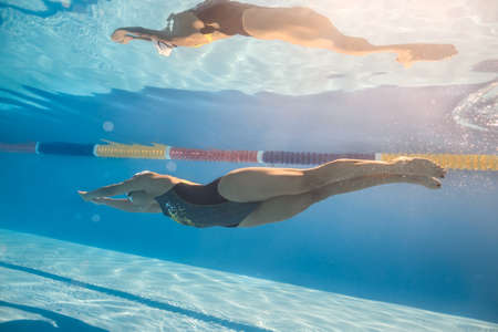 swim cap: Good swimmer swims in crawl style underwater in the swim pool outdoors. She wears black-gray swimsuit, white swim cap and swim glasses. Sunlight falls from above. Her body reflected in water surface. Stock Photo