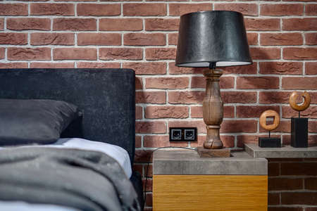 coverlet: Old style wooden lamp with black lampshade on the rack on the brick wall background. On the right there is rack with decorations. On the left there is bed with pillow and coverlet. Horizontal. Stock Photo