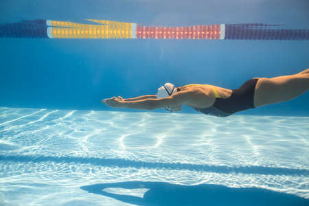 swim cap: Nice woman swims in crawl style underwater in the swimming pool outdoors. She wears a black-gray swimsuit with patterns, a white swim cap and swim glasses. Sunlight falls from above. Horizontal.