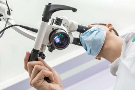 Close-up bottom view of a glowing dental microscope and a doctor who is using it. Man wears a blue medical mask. Horizontal.