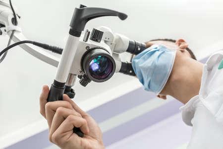 Primer plano vista desde abajo de un microscopio dental brillante y un médico que lo está utilizando. El hombre lleva una máscara médica azul. Horizontal.