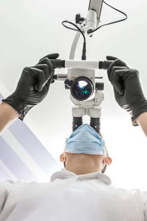 rational: Rational doctor is using the dental microscope in the clinic. He is wearing a white uniform, black gloves and a blue medical mask. The microscope is glowing. View from the bottom. Vertical.