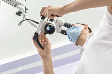 Capable doctor is using the dental microscope in the clinic. He is wearing a white uniform and a blue medical mask. The microscope is glowing. View from the bottom. Horizontal. Stock Photo