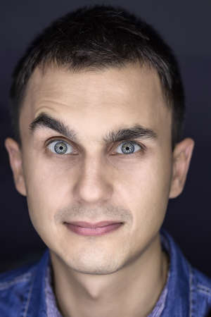 grimaces: Amusing macro portrait of a young guy on the dark background. He grimaces and looks into the camera with a smile. Vertical. Stock Photo