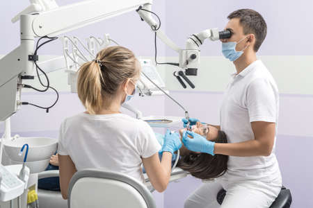 Woman in goggles on a dental chair and a dentist with assistant who sit next to her. Man looks on her teeth using a dental microscope and holds dental instruments. Blonde holds an air water syringe. Standard-Bild