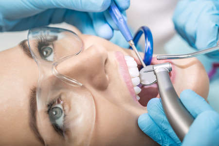 Macro photo of the teeth treatment in the dentists office. Girl with open mouth in a protective glasses, hands in blue medical gloves with dental instruments next to her mouth. Horizontal.
