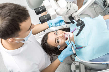 Girl in protective glasses and a patient bib on a patient chair and a dentist who sits next to her. Man holds a dental handpiece and a mirror near her mouth. Dental microscope is over the patient.