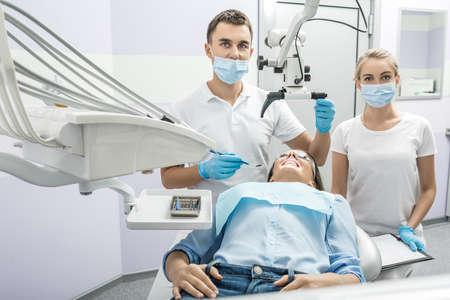dentiste intelligent et un assistant côtoient fille sur une chaise de patient dans le cabinet d'un dentiste. Doctor est titulaire d'un microscope dentaire et un miroir dentaire. Ils use uniforme blanc avec des masques bleus et des gants.