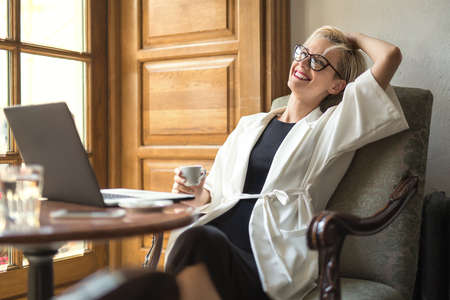 leans on hand: Dreamy blonde girl in glasses sits on the armchair at the table with a laptop in the cafe. She leans on armchair with a smile and holds a cup in right hand. Woman wears black dress and a white cloak.