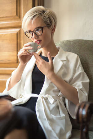 enchanting: Enchanting blonde girl with a smile in glasses sits on the armchair at the table in the restaurant. She holds a cup in her hands and looks to the side. Woman wears a black dress and a white cloak. Stock Photo