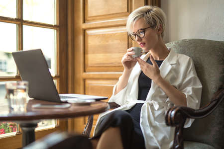 delightful: Delightful blonde girl with a smile in glasses sits on the armchair at the table in the restaurant. She holds a cup in the hands and looks at the laptop. Woman wears black dress and a white cloak.