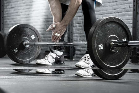 legs around: Photo of mans hands near the barbell on the background of his legs in black pants and white-black sneakers. Guy holds the hands together. Cloud of sport powder is around guys hands. Close-up.