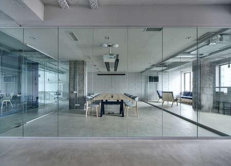 Biuro w stylu loftu z białymi murami i betonowymi kolumnami. Jest strefa konferencyjna z dużą drewnianą stołem z szarymi krzesłami i przegrodami ze szkła. Nad stołem znajduje się projektor.