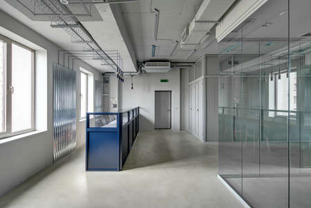 Blue metal reception rack with armchairs in a loft style office with gray walls. There is an entrance door and work zones with glass and mesh partitions. Table with chairs are reflected in the glass. Фото со стока