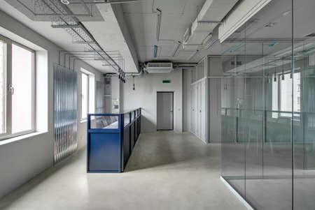 estante azul de recepción de metal con sillones en una oficina tipo loft con paredes grises. Hay una puerta de entrada y las zonas de trabajo con vidrio y malla de particiones. Mesa con sillas se refleja en el cristal.