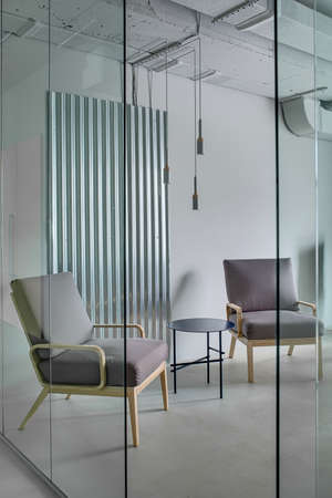 glass partition: Armchairs with wooden legs and a small round metal table on the background of the gray wall with the metal panel. In front of them  there is a glass partition with an entrance. Indoors. Vertical. Stock Photo