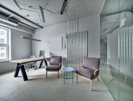 Gray room in a loft style with a glass partition with glass door. There is a long wooden table with a computer, armchairs, a small round table and a metal panel on the back wall. Horizontal.