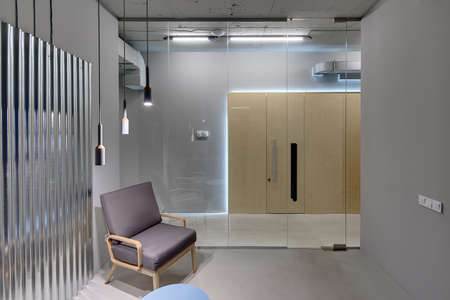 glass partition: Business interior in a loft style with gray walls. There is a room with a glass partition with door, an armchair, a small table and a metal panel on the wall. Opposite the room there are wooden doors. Stock Photo