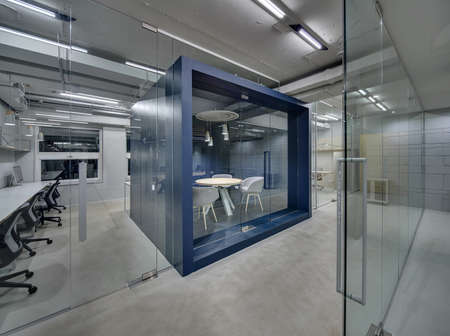 Donkerblauwe vergaderzaal met meubels en glazen deur op kantoor in houten stijl met grijze muren. Rondom zijn er werkzones met glaswanden. Lampen gloeien. Horizontaal.