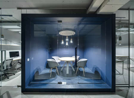 interior walls: Meeting room with blue walls and furniture and a glass door in the office in a loft style with gray walls. Around it there are work zones with glass and mesh partitions. Lamps are glowing. Horizontal. Stock Photo