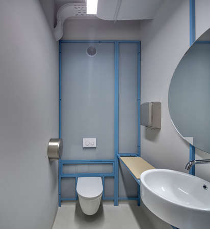 Lavatory in a loft style with the glowing lamps and gray walls  There is a. Lavatory In A Loft Style With The Glowing Lamps And Gray Walls