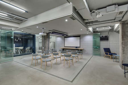 Zone for presentations in office in a loft style with brick walls and concrete columns. Zone has many gray chairs and a projector above them. On the left there is blue meeting zone with glass doors.