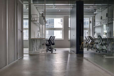 partitions: Business interior in a loft style with gray walls and gray floor. There are workplaces with black armchairs and tabletops with computers. They divided with black wall and glass partitions and doors.