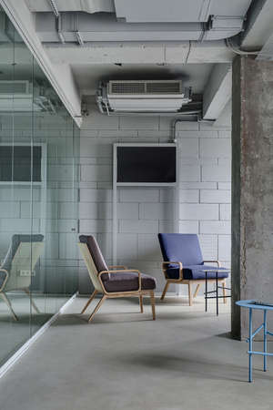 partitions: Interior in the office in a loft style with a light brick wall. There are metal round tables and multi-colored armchairs with wooden legs between a concrete column and glass partitions. Vertical. Stock Photo