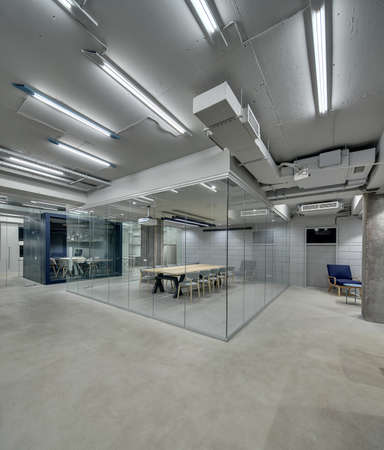 Bright office in a loft style with glowing lamps, gray brick walls and concrete columns. There are zones with furniture for meeting and conference which fenced with glass partitions. Vertical.