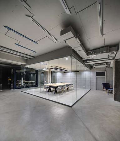 partitions: Office in a loft style with glowing lamps, light brick walls and concrete columns. There is a meeting zone with a large wooden table with gray chairs and glass partitions. Vertical.