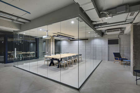 Luminous conference zone in the office in a loft style with brick walls and concrete columns. Zone has a large wooden table with gray chairs and glass walls. Above the table there is a projector. Stockfoto
