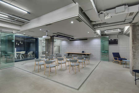 Presentation zone in the office in a loft style with brick walls and concrete columns. Zone has many gray chairs and a projector above them. On the left there is blue meeting zone with glass doors.