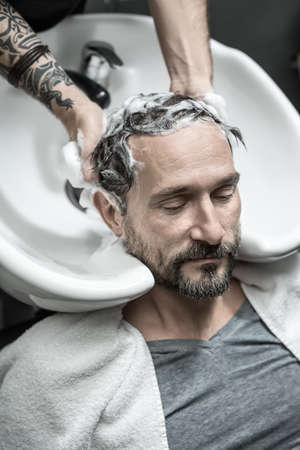 shampooing: Pacified man with a beard lies on the white sink in the barbershop. Barber with a tattoo is shampooing his head. Guy wear a gray T-shirt and a towel. Closeup. Vertical.