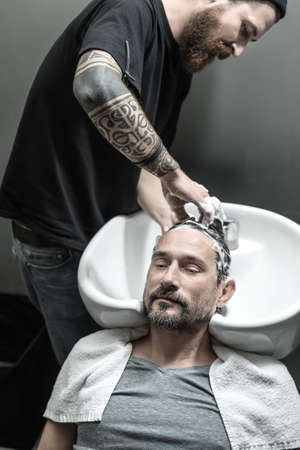 shampooing: Relaxed man with a beard lies on the white sink in the barbershop. Brutal barber with a tattoo and a big beard is shampooing his head. Guy has a white towel. Vertical.