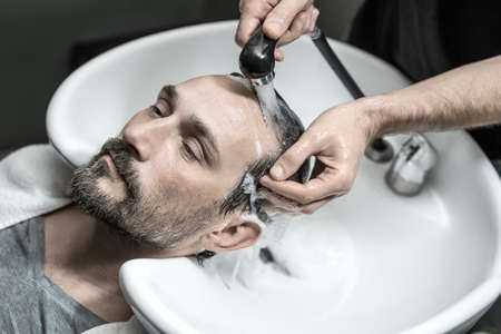 cute guy: Cute man with a beard lies on the white sink in the barbershop. Barber washes his head with the black faucet. Guy wears a gray T-shirt and a white towel. Closeup. Horizontal.