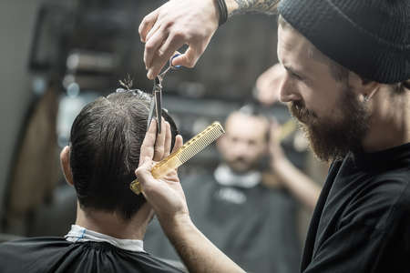 Trendy barber with a big beard and a tattoo is cutting the hair of his client in the black cape in the barbershop. He has a hair comb and scissors. They blurry reflected in a mirror. Horizontal.