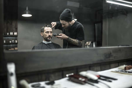 peerless: Peerless barber with a beard and a tattoo is cutting the hair of his bearded client in the barbershop. He is using a cutting comb and a hair clipper. Customer has hairgrips on the head. Horizontal.