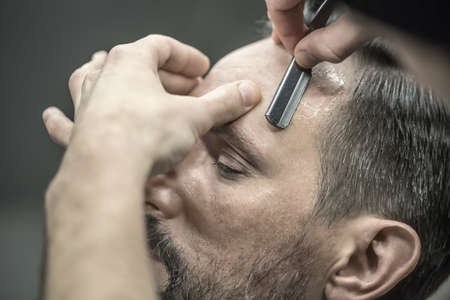 straight man: Bearded man in the barbershop. Barber is trimming his hair with a straight razor. Closeup. Horizontal.